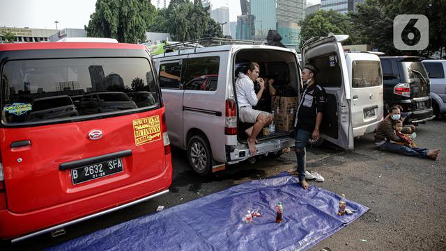 Penumpang kendaraan travel gelap yang disita jajaran Direktorat Lalu Lintas Polda Metro Jaya sedang istirahat, Jakarta, Kamis (29/4/2021). Sebanyak 115 kendaraan travel gelap diamankan karena diduga kuat mengangkut pemudik di tengah masa pengetatan larangan mudik 2021. (Liputan6.com/Faizal Fanani)