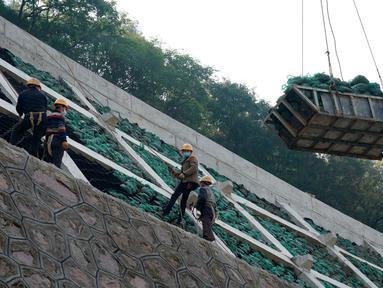 Para pekerja sedang meletakkan kantong-kantong ramah lingkungan berisi tanah dan benih di sebuah lereng untuk gelaran Olimpiade Musim Dingin Beijing 2022 di Distrik Yanqing, Beijing, ibu kota China (28/9/2020). (Xinhua/Zhang Chenlin)