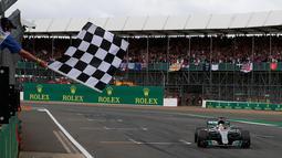 Lewis Hamilton berhasil finish diurutan pertama pada GP Inggris di sirkuit Silverstone, (16/7).  Hamilton mengungguli rekan setimnya Valtteri Bottas (Finlandia), dan pebalap Scuderia Ferrari, Kimi Raikkonen (Finlandia). (AP Photo/Jason Cairnduff, Pool)