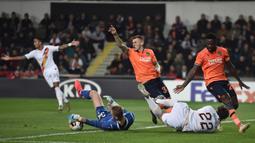 Gelandang AS Roma Nicolo Zaniolo berebut bola dengan kiper Istanbul Basaksehir, Mert Gunok pada laga kelima Grup J Liga Europa 2019-2020 di stadion Fatih Terim, Kamis (28/11/2019). AS Roma menang meyakinkan dengan skor 3-0.  (Ozan KOSE / AFP)