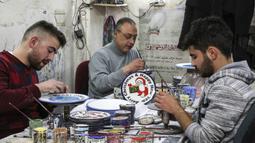 Sejumlah pekerja Palestina menyelesaikan pembuatan piring keramik bergambar hiasan bertema Natal di sebuah pabrik keramik di kota titik nyala Hebron di Tepi Barat (17/12/2019). (AFP/Hazem Bader)