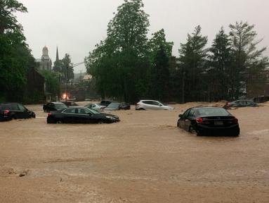 Sejumlah mobil terjebak dalam banjir yang menggenangi Ellicott City, Maryland (27/5). Banjir bandang melanda kota Maryland pada Minggu (27/5) waktu setempat. (Kenneth K. Lam / The Baltimore Sun via AP)