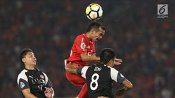 Pemain Persija, Riko Simanjuntak (tengah) berebut bola dengan pemain Home United saat laga kedua Semifinal Zona Asia Tenggara Piala AFC 2018 di Stadion GBK, Jakarta, Selasa (15/5). Babak pertama Persija tertinggal 1-3. (Liputan6.com/Helmi Fithriansyah)