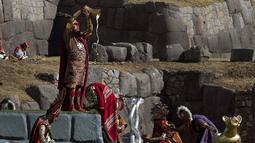 "Aktor David Ancca yang berperan sebagai Kaisar Inca memainkan adegan menumpahkan minuman yang disebut ""chicha"" saat upacara Inca ""Inti Raymi"" di reruntuhan Saqsaywaman di Cuzco, Peru (24/6). (AP/Martin Mejia)"