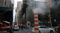 Pemandangan kebakaran yang melanda Trump Tower di New York, Amerika Serikat, Sabtu (7/4). Korban tewas merupakan salah satu penghuni gedung bertingkat 50 milik Donald Trump itu. (AP Photo/Craig Ruttle)