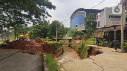 Jalan ambles di ruas Jalan Boulevard, Grand Depok City (GDC), Kota Depok, Jawa Barat, Selasa (13/4/2021). Jalan tersebut ambles ke aliran sungai sedalam 3 hingga 5 meter. (Liputan6.com/Herman Zakharia)
