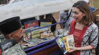 Duta Baca Indonesia, Najwa Shihab berbincang dengan Kimong pemilik bemo yang dijadikan perpustakaan di RTPRA Kalijodo, Jakarta, Selasa (2/5). (Liputan6.com/Yoppy Renato)