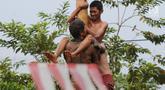 Para peserta berjibaku lumpur dan oli mengikuti lomba panjat pinang di Perumahan Griya Pamulang 2, Tangerang Selatan, Jumat (17/8). Lomba yang diselengarakan oleh Bina Remaja ini dalam rangka memeriahkan HUT Ke-73 RI. (Merdeka.com/Dwi narwoko)