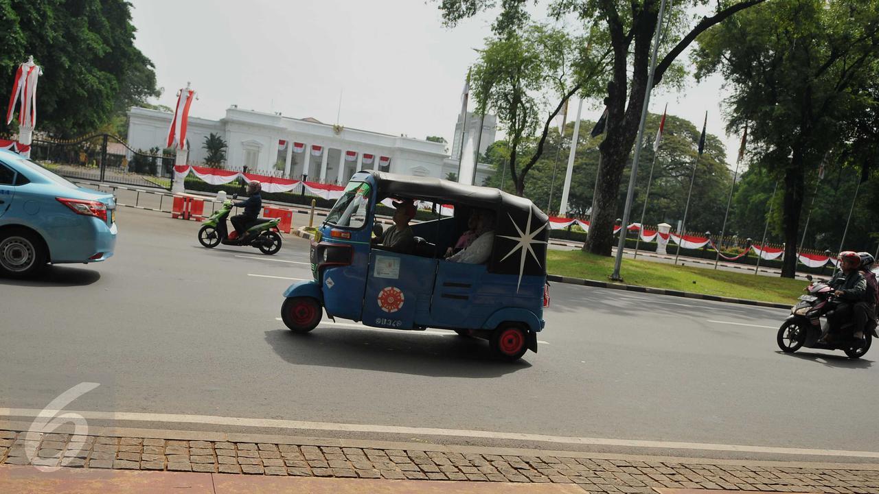 Angkutan umum jenis bajaj melintas di depan Istana Kepresidenan, Jakarta, Rabu (20/7). Picu kemacetan, Sudinhubtrans Jakarta Pusat segera menerapkan larangan bajaj melintas di Jalan Medan Merdeka Barat dan Medan Merdeka Utara (Liputan6.com/Gempur M Surya)