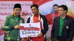 Pelari muda Indonesia, Lalu Muhammad Zohri (tengah) menerima bonus dari Menpora Imam Nahrawi di Terminal 3 Bandara Soetta, Tangerang, Selasa (17/7). Lalu M Zohri meraih emas lari 100m putra di Kejuaraan Dunia U-20 IAAF. (Liputan6.com/Helmi Fithriansyah)
