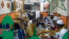 Para imigran Pakistan menikmati makanan sahur sebelum beribadah puasa di distrik Kwai Chung di Hong Kong (25/5/2019). Kwai Chung adalah daerah perkotaan di dalam Kota Baru Tsuen Wan di Wilayah Baru Hong Kong. (AFP Photo/Philip Fong)