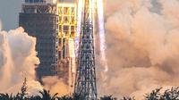 Roket Long March 5B membawa modul inti Stasiun Luar Angkasa Tianhe lepas landas dari Pusat Peluncuran Luar Angkasa Wenchang di Provinsi Hainan, China, Rabu (29/4/2021). Baru pada tahun 2003 China mengirim astronot pertamanya ke orbit. (STR/AFP)