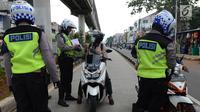 Anggota Satlantas Jakarta Timur merazia sepeda motor yang masuk jalur Transjakarta di kawasan Jatinegara, Jakarta, Kamis (7/2). Pelanggaran ini sering terjadi pada pagi hari. (Merdeka.com/Imam Buhori)