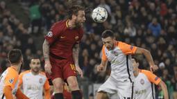 Kapten AS Roma, Daniele de Rossi menyundul bola melewati adangan pemain Shakhtar, Ivan Ordets pada leg kedua 16 besar Liga Champions di Rome Olympic stadium, (13/3/2018). AS Roma Menang 1-0. (AP/Gregorio Borgia)