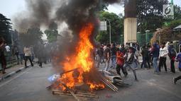 Pelajar membakar sepeda motor dan rambu lalu lintas saat berdemonstrasi di belakang Gedung DPR, Palmerah, Jakarta, Rabu (25/9/2019). Polda Metro Jaya mengamankan 200 pelajar yang berdemonstrasi. (Liputan6.com/Angga Yuniar)