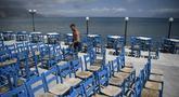 Seorang karyawan menyiapkan teras di Kissamos, barat laut Pulau Kreta, Yunani, Kamis (13/5/2021). Yunani mempermudah langkah-langkah terkait COVID-19 dalam menyambut turis internasional pada 14 Mei. (Louisa GOULIAMAKI/AFP)