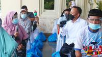 CEO PTPN V Jatmiko K Santosa berbincang dengan penyandang disabilitas di Pekanbaru ketika menyalurkan 2.000 paket sembako. (Liputan6.com/M Syukur)