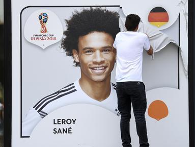 Seorang petugas menurunkan gambar Leroy Sane dari dinding museum sepakbola di Dortmund, (4/6/2018). Pelatih Joachim Low tidak memasukan nama Leroy Sane dalam skuat Der Panzer untuk Piala Dunia 2018. (Federico Gambarini/dpa via AP)
