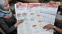 Petugas Komisi Pemilihan Umum (KPU) memperkenalkan contoh lima surat suara Pemilu 2019 di Gedung KPU, Jakarta, Senin (10/12). Pemilu 2019 akan diawasi oleh Bawaslu. (Merdeka.com/Iqbal Nugroho)