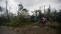 Pengendara melintas di dekat pohon yang tumbang setelah Badai Matthew menghantam wilayah Les Cayes di Haiti (4/10). Badai Matthew ini telah mengakibatkan banjir, banyak pohon tumbang dan ratusan rumah warga rusak parah. (REUTERS/Andres Martinez Casares)