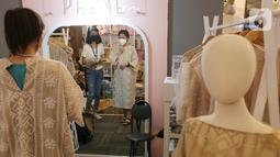 Pengunjung mencoba pakaian dalam pameran Market Museum 'REVIVE' di Lippo Mall Kemang, Minggu (06/05/2021). Pameran hari terakhir yang diikuti 54 peserta, terdiri dari 40 fesyen dan 15 kuliner menjadi kebangkitan semangat UMKM di tengah pandemi. (Liputan6.com/Fery Pradolo)
