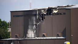 Kerusakan terlihat setelah pesawat bermesin ganda menabrak hanggar di Bandara Addison, Addison, Texas, AS,  Minggu (30/6/2019). Sumber CBS News mengatakan pesawat kehilangan kendali mesin saat lepas landas dan berbelok ke arah hanggar. (Shaban Athuman/The Dallas Morning News via AP)