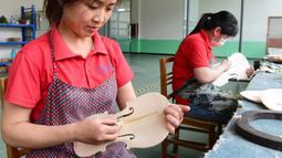 Para pekerja membuat biola di sebuah bengkel kerja di Queshan, Provinsi Henan, China, Rabu (20/5/2020). Kawasan industri penghasil alat musik tersebut mampu memproduksi 30.000 biola dan selo setiap tahun. (Xinhua/Zhu Xiang)