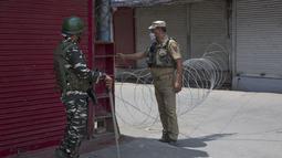 Seorang polisi India (kanan) memblokade sebuah jalan saat penerapan karantina wilayah (lockdown) guna membendung penyebaran pandemi COVID-19 di Kota Srinagar, ibu kota musim panas Kashmir yang dikuasai India (26/7/2020). (Xinhua/Javed Dar)