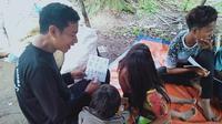 Gentar Tampung (kiri) mengajari mengenal huruf dan angka bagi anak-anak rimba di wilayah pedalaman Makekal Ilir, Kabupaten Tebo, Jambi, Kamis (19/11/2020). Gentar menjadi salah satu kader pendidikan bagi anak-anak rimba. (Liputan6.com/Gresi Plasmanto)