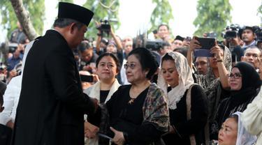 Presiden ke-6 RI Susilo Bambang Yudhoyono bersalaman dengan Presiden ke-5 RI Megawati Soekarnoputri usai prosesi pemakaman Ani Yudhoyono di TMP Kalibata, Jakarta, Minggu (2/6/2019). SBY mengucapkan terima kasih kepada Megawati yang menghadiri prosesi pemakaman Ani Yudhoyono. (Liputan6.com/HO/Rangga)