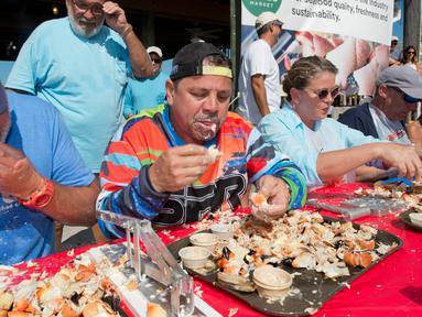 Para peserta beradu cepat memakan daging kepiting batu dalam kontes Key Fisheries Stone Crab Eating di Marathon, Florida, Sabtu (10/11). Mereka harus memecahkan cangkang 25 kepiting batu lalu memakan dagingnya. (Andy Newman/Florida Keys News Bureau/AFP)