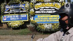 Warga melintas di depan karangan bunga tanda duka cita atas meninggalnya mantan KSAD Jenderal TNI (Purn) Pramono Edhie Wibowo di kawasan Puri Cikeas, Kab Bogor, Jabar, Minggu (14/6/2020). Pramono Edhie Wibowo wafat di usia 65 tahun akibat serangan jantung. (Liputan6.com/Helmi Fithriansyah)
