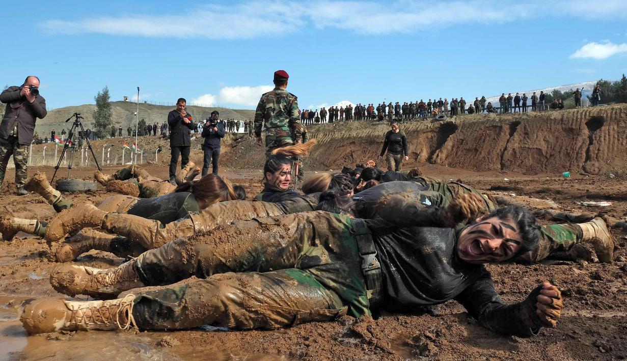 Pasukan perempuan Peshmerga menggulingkan badannya di tanah saat berlatihan dalam upacara kelulusan di Kota Soran, Irak, Rabu (12/2/2020). Latihan militer pasukan bersenjata Kurdi tersebut dilakukan sekitar 100 kilometer timur laut ibu kota otonomi wilayah Kurdi di Irak, Arbil. (SAFIN HAMED/AFP)