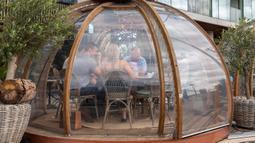 Para pelanggan bersantap di bawah kanopi di sebuah restoran yang diatur untuk memisahkan kelompok pengunjung yang berbeda agar tetap aman dengan mengikuti pedoman pemerintah untuk COVID-19 di London, Inggris, pada 12 September 2020. (Xinhua/Han Yan)