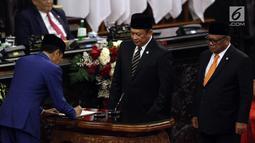 Presiden Joko Widodo menandatangani RUU tentang APBN TA 2020 beserta Nota Keuangan dan pendukungnya disaksikan Ketua DPR Bambang Soesatyo dan Ketua DPD Oesman Sapta Odang dalam Sidang Paripurna di Gedung DPR, Jakarta, Jumat (16/8/2019). (Liputan6.com/JohanTallo)