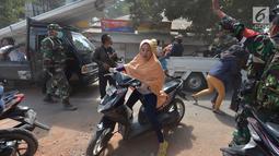 Seorang wanita menggunakan sepedah motor menyelamatkan diri saat terjadi gempa susulan di Tanjung pulau Lombok, NTB, Kamis (9/8).Gempa susulan tersebut menyebabkan kepanikan di antara pengungsi yang berlindung.(AFP/ ADEK BERRY)