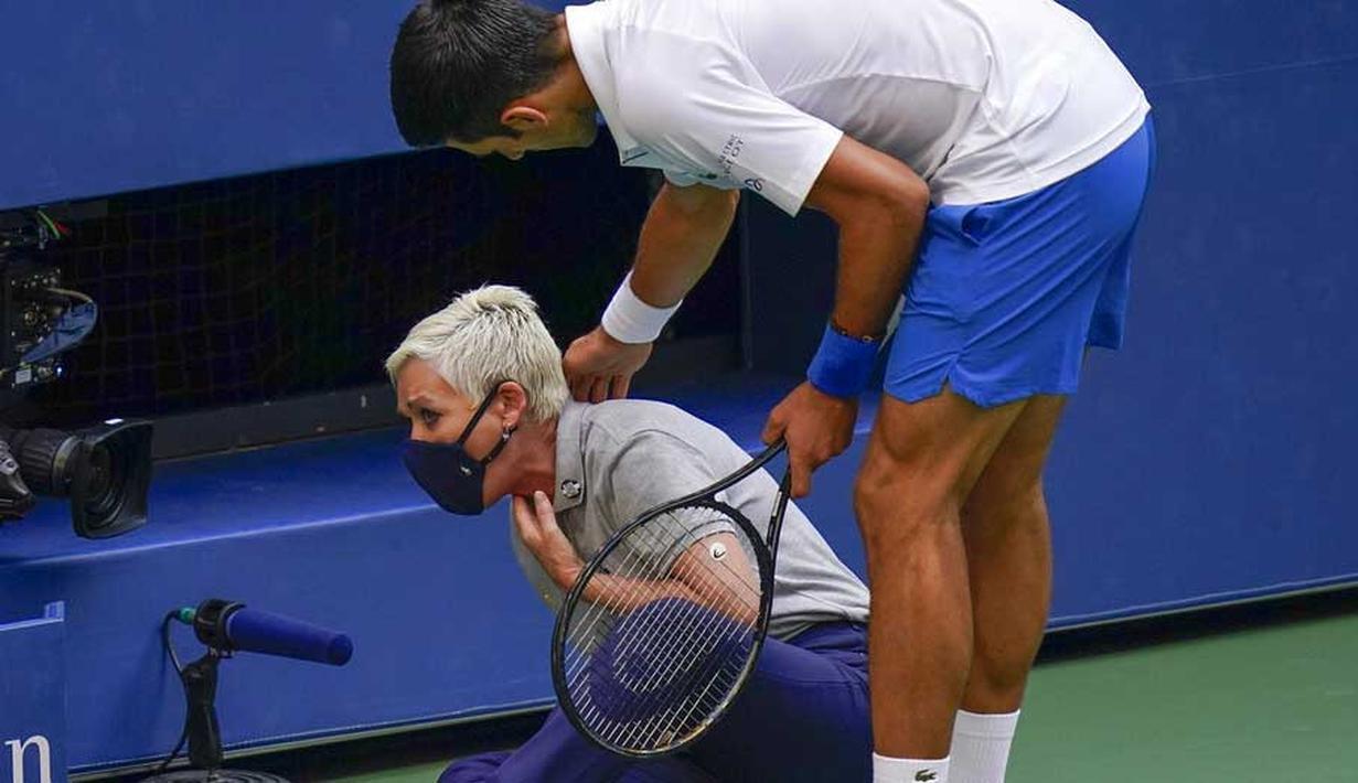 Petenis Serbia, Novak Djokovic, menghampiri hakim garis yang terkena bola pada AS Terbuka di Flushing Meadows, Senin (7/9/2020). Djokovic didiskualifikasi karena memukulkan bola tenis ke arah hakim garis. (AP/Seth Wenig)