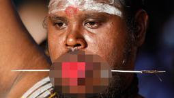 Seorang umat Hindu menusukkan besi ke pipinya saat Festival Thaipusam di Batu Caves, Kuala Lumpur, Malaysia, Rabu (31/1). Thaipusam adalah prosesi tahunan umat Hindu. (AP Photo/Sadiq Asyraf)