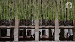 Aktivitas jemaah di salah satu lorong yang kini dihiasi tanaman gantung di Masjid Istiqlal, Jakarta, Senin (22/2/2021). Wajah baru Masjid Istiqlal terasa lebih indah ketika menjelang malam dengan ornamen lampu yang menghiasi seluruh kompleks masjid. (merdeka.com/Iqbal S Nugroho)