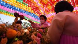 Seorang umat Buddha menuangkan air ke patung Buddha saat upacara merayakan ulang tahun Buddha di Kuil Jogye, Seoul, Korea Selatan, Rabu (19/5/2021). Umat Buddha mengunjungi kuil di seluruh negeri untuk merayakannya ulang tahun Sang Buddha. (AP Photo/Lee Jin-man)