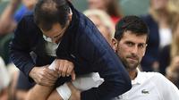 Ekspresi Novak Djokovic ketika mendapat perawatan medis pada lengan kanan saat melawan Adrian Mannarino pada Wimbledon 2017 di The All England Lawn Tennis Club, London, (11/7/2017). (AFP/Glyn Kirk)