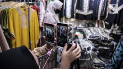 Pedagang menunjukkan sejumlah pakaian melalui aplikasi online (daring) di Pasar Tanah Abang, Jakarta, Rabu (1/7/2020). Pedagang Pasar Tanah Abang mulai menjual barang secara daring untuk menambah penjualan dan mengantisipasi turunnya jumlah pembeli di masa PSBB Transisi. (Liputan6.com/Faizal Fanani)