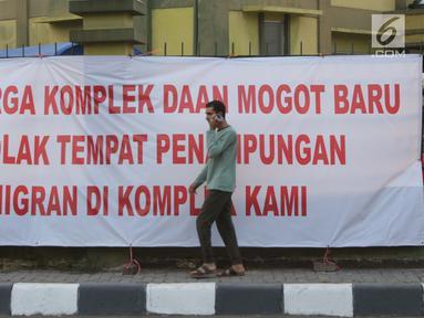 Salah satu pencari suaka melintasi spanduk penolakan di depan bekas Markas Kodim di Kalideres, Jakarta, Selasa (16/7/2019). Sebelumnya, para pencari suaka dari berbagai negara berkonfilk ini tinggal di pinggir jalan dan trotoar di kawasan Kebon Sirih, Jakarta. (Liputan6.com/Helmi Fithriansyah)