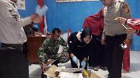 Nampak beberapa anggota polsek dan koramil Cikajang membuka tas mencurigakan berisi jenazah bayi perempuan (Liputan6.com/Jayadi Supriadin)