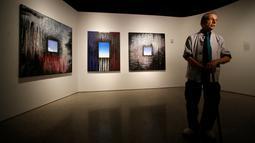 Seniman Ejay Weiss berdiri di depan karya lukisnya berjudul '9/11 Elegies' yang dipamerkan di National September 11 Memorial and Museum, Manhattan, AS (1/9). Pameran ini diikuti oleh 13 seniman asal New York. (REUTERS/Andrew Kelly)