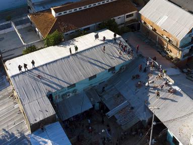 Narapidana melemparkan batu ke arah polisi dari atap penjara Tacumbu saat kerusuhan di Asuncion, Paraguay, Selasa (16/2/2021). Menurut Kementerian Kehakiman Paraguay, enam narapidana tewas dalam kerusuhan di penjara Tacumbu. (AP Photo/Jorge Saenz)