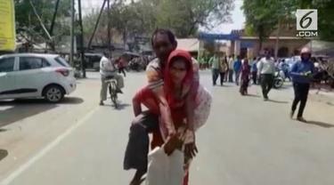 Seorang istri rela menggendong suaminya dan berjalan jauh untuk mendapatkan sebuah kursi roda.