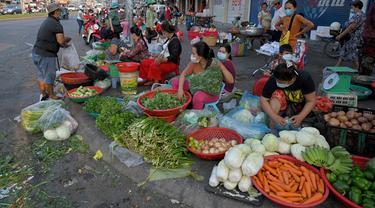 Pedagang menyiapkan sayuran untuk dijual di sepanjang jalan karena pasar tetap tutup di tengah pembatasan lockdown yang diberlakukan untuk mencoba menghentikan lonjakan kasus virus corona COVID-19 di Phnom Penh, Kamboja, Selasa (11/5/2021). (TANG CHHIN Sothy/AFP)