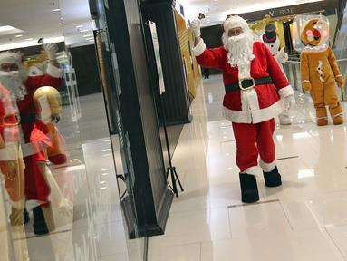 Petugas yang mengenakan kostum Sinterklas berkeliling saat menghibur pengunjung di Senayan City Mall, Jakarta, Jumat (25/12/2020). Kegiatan tersebut bertujuan untuk melengkapi kebahagiaan Natal tahun 2020. (Liputan6.com/Herman Zakharia)
