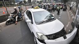 Pengendara sepeda motor tersendat saat melintasi lokasi kecelakaan taksi menabrak tiang di Jalan Ahmad Yani, Jakarta, Rabu (1/8). Tidak ada korban jiwa dalam kecelakaan tersebut. (Merdeka.com/Iqbal Nugroho)